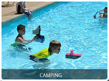 two boys racing cardboard boats in the swimming pool with link to the camping page