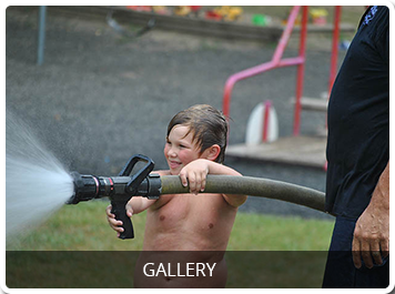 child spraying a firehose referencing to the photo gallery page
