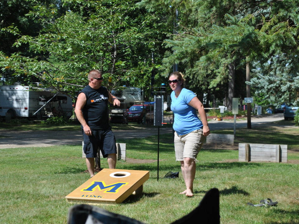 man and woman playing horseshoes at gateway park campground in mi